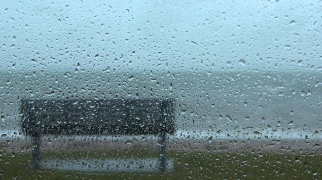 Blick durch eine Fensterscheibe in den Regen, zu sehen ist eine Bank.