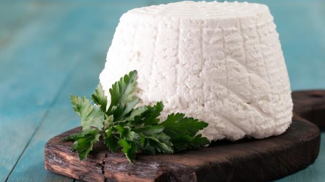 Man sieht einen Ricotta-Käse auf einem Holzbrett.