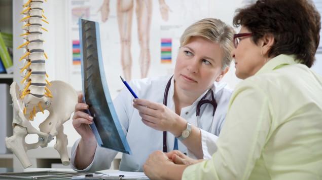 Eine Ärztin zeigt ihrer Patientin ein Röntgenbild.