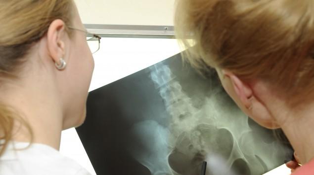 Eine Ärztin betrachtet mit ihrer Patientin eine Röntgenaufnahme des Beckens.