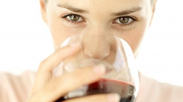 Das Bild zeigt eine Frau mit einem Glas Rotwein.