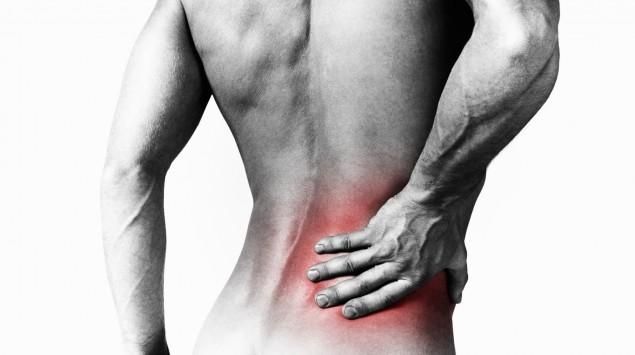 Ein Mann fasst sich an den unteren Rücken (schematische Darstellung).