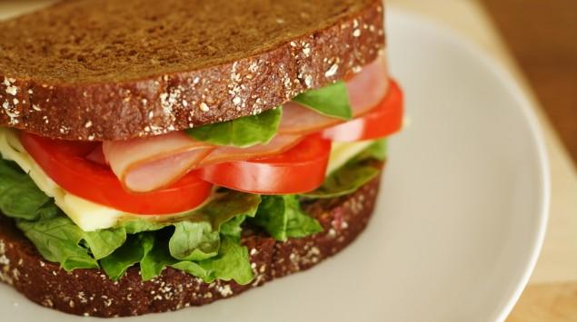 Das Bild zeigt ein Vollkornsandwich mit Käse, Salat, Tomaten und Putenbrust.