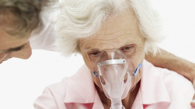 Eine ältere Frau bekommt eine Sauerstoffmaske.