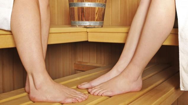 Man sieht zwei Paar Beine in einer Sauna.