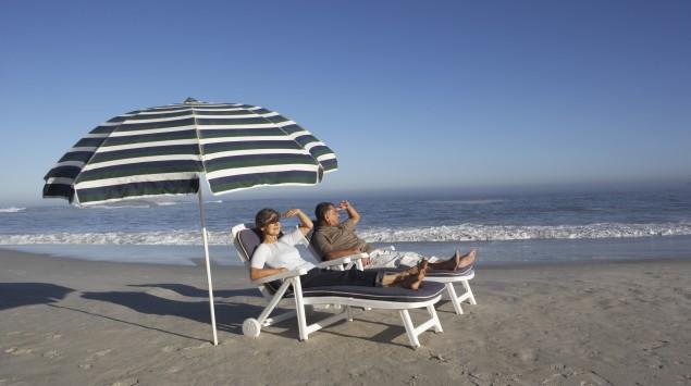 Das Bild zeigt ein Paar am Meer, das in Liegestühlen unter einem Sonnenschirm liegt.
