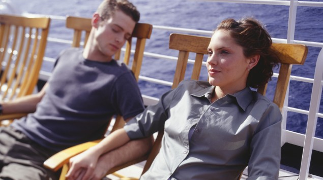 Das Bild zeigt einen schlafenden Mann und eine Frau in Liegestühlen auf dem Deck eines Schiffs.