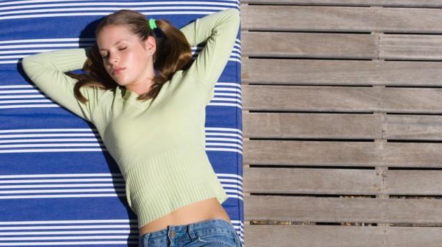 Das Bild zeigt ein Mädchen, das am Deck eines Schiffes schläft.