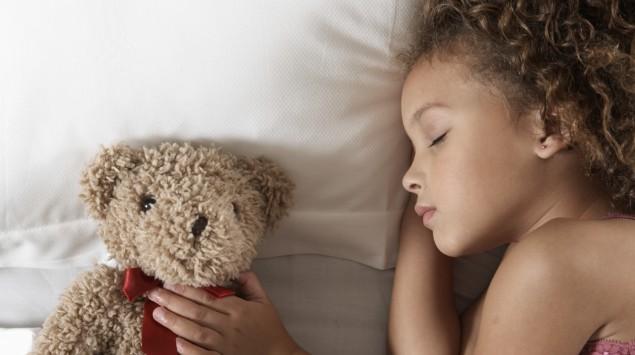Mädchen liegt schlafend im Bett, daneben ein Teddy.