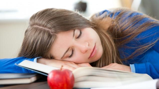 Ein Mädchen hat den Kopf auf seine Bücher gelegt und schläft am Schreibtisch.