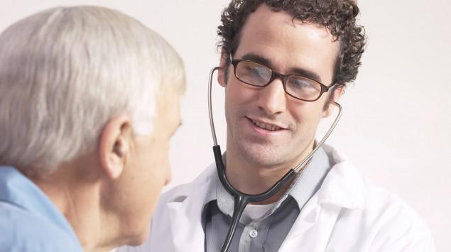 Ein junger Arzt horcht einen alten Patienten ab.
