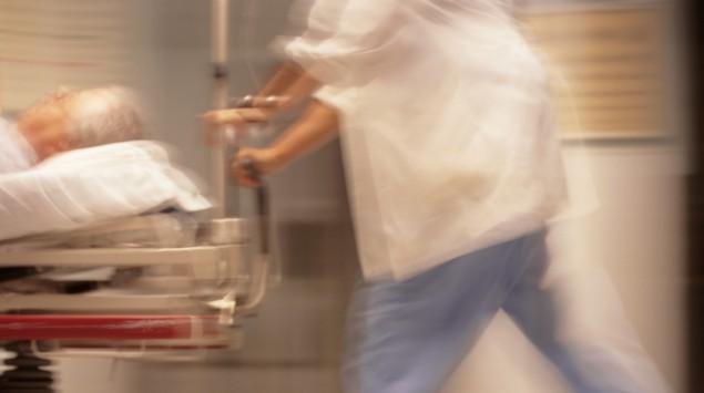 Ein Pfleger schiebt einen Patienten im Bett schnell über Krankenhausgänge.