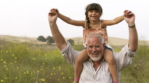 Ein älterer Mann trägt seine Enkelin auf den Schultern.
