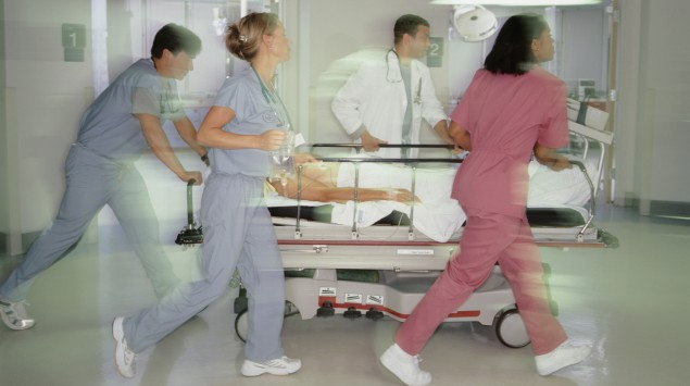 Rettungskräfte schieben Krankenbett durch Krankenhauskorridore.