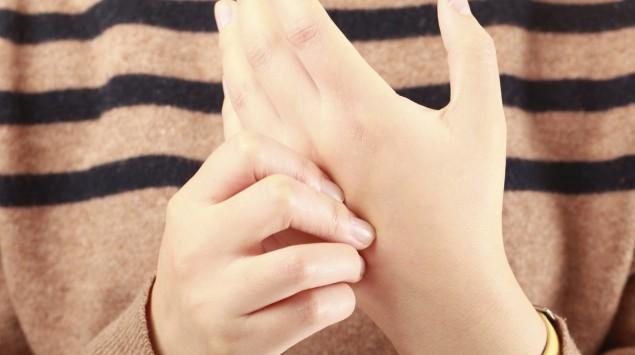 Man sieht eine Frau, die sich die Hände reibt.