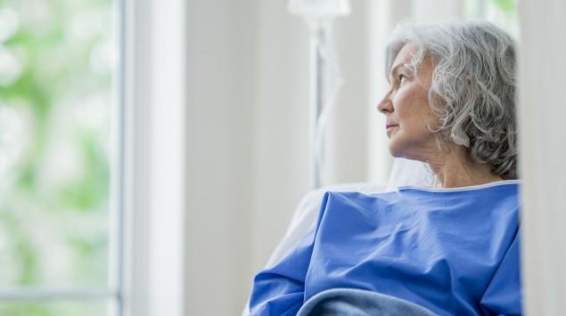 Eine ältere Frau in einem Bett mit Infusion.