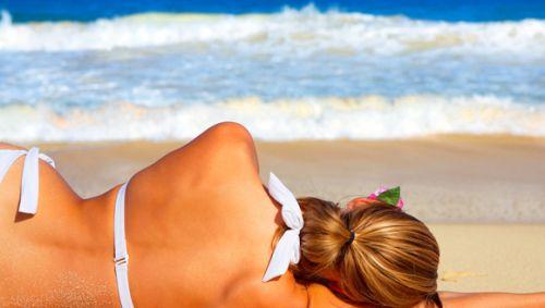 Die Rückansicht einer Frau, die im Bikini am Strand liegt.