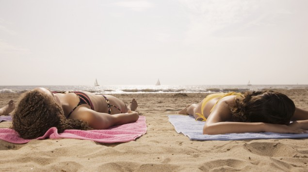 Das Bild zeigt Teenager, die am Strand liegen und sich sonnen.