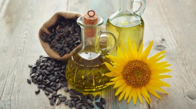 Man sieht Sonnenblumenkerne, eine Sonnenblumenblüte und zwei Flaschen Öl.