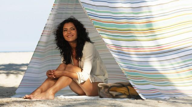 Das Bild zeigt eine junge Frau, die sich unter einem Zelt vor der Sonne schützt.