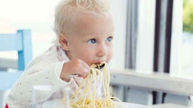 Ein Mädchen isst Spaghetti.