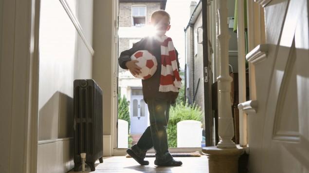Ein Junge steht mit einem Ball in der Tür.