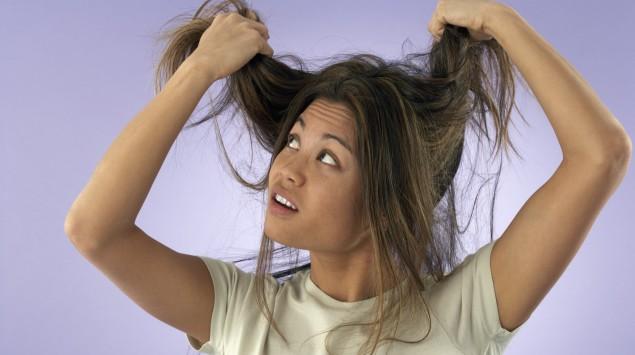 Das Bild zeigt ein Mädchen, das seine Haare betrachtet.