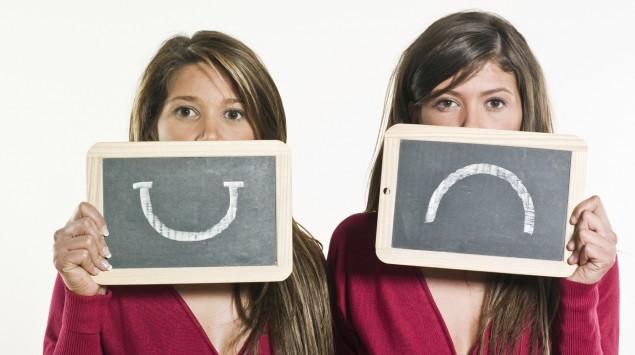 Zwei gleich gekleidete Frauen, eine hält ein Schild mit einem lachenden, die andere ein Schild mit einem traurigen Smiley hoch.