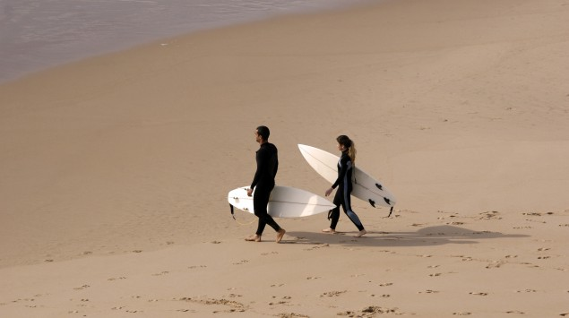 Zwei Surfer laufen am Strand entlang.