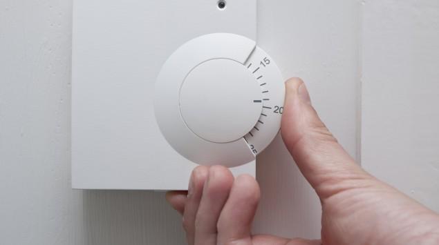 Eine Hand stellt einen Thermostat ein.