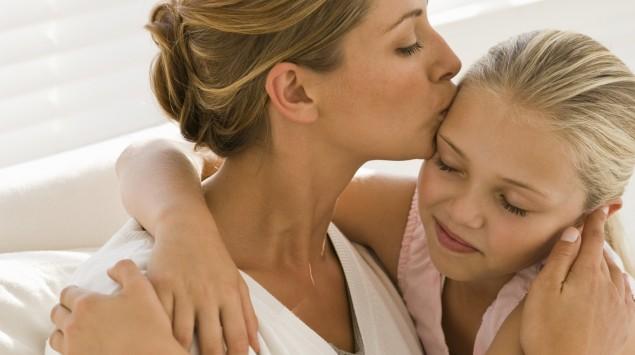 Eine Frau küsst ihre Tochter.
