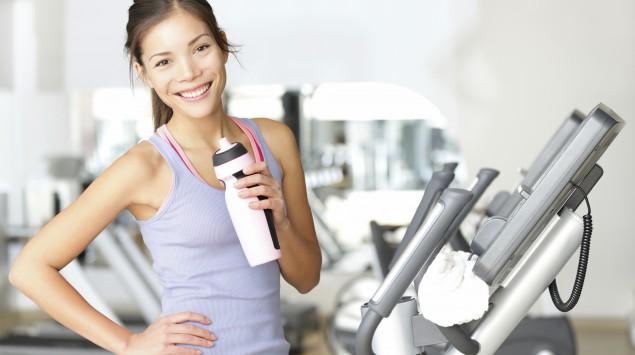 Eine Frau steht im Fitnessstudio und hält eine Trinkflasche in der Hand.