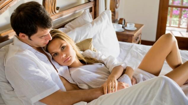 Ein Paar im Bett, der Mann hält die Frau im Arm.