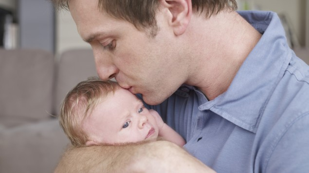 Ein Mann küsst ein kleines Baby.