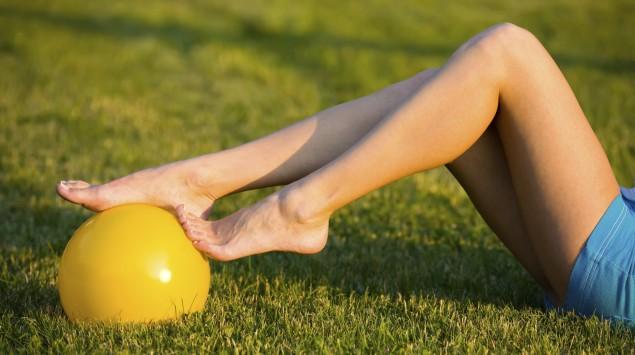 Die Beine einer Frau, die auf einer Wiese liegt, daneben liegt ein Gymnastikball.