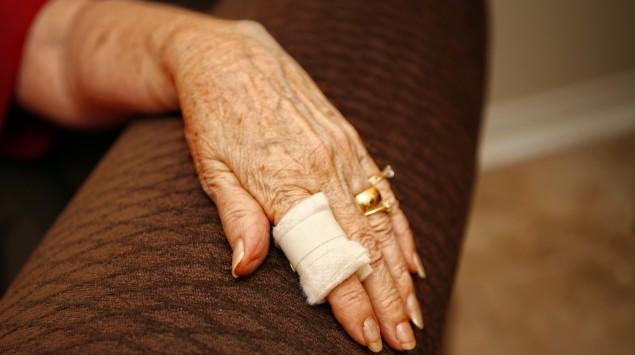 Man sieht die Hand einer alten Frau, ein Finger trägt einen Verband.