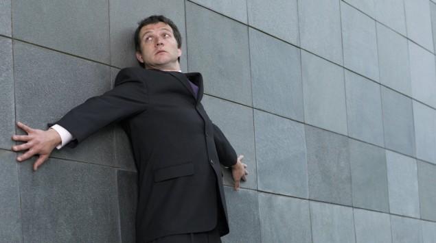 Ein Mann in Geschäftskleidung lehnt ängstlich an einer Wand.