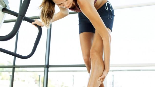 Es ist eine Läuferin zu sehen, die sich auf einem Laufband stehend die Wade hält