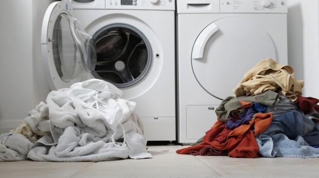 Das Bild zeigt eine Waschmaschine mit Wäsche davor.