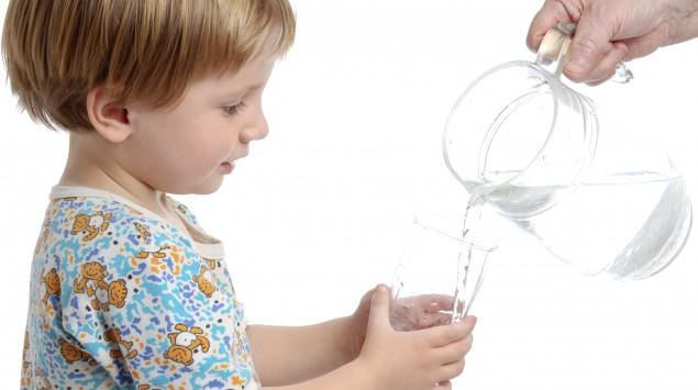 Ein Junge bekommt Wasser in ein Glas eingeschenkt.
