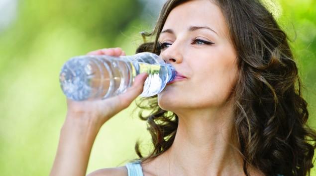 Eine Frau trinkt ein Glas Wasser.