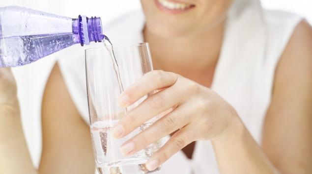 Eine Frau gießt Mineralwasser in ein Glas.