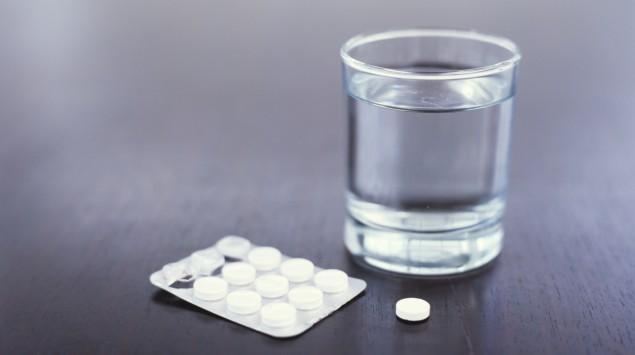 Man sieht ein Glas mit Wasser und Tabletten.