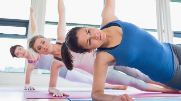 Drei Frauen füren eine Yoga-Übung aus.