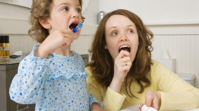 Eine Mutter übt mit ihrer Tochter Zähneputzen.