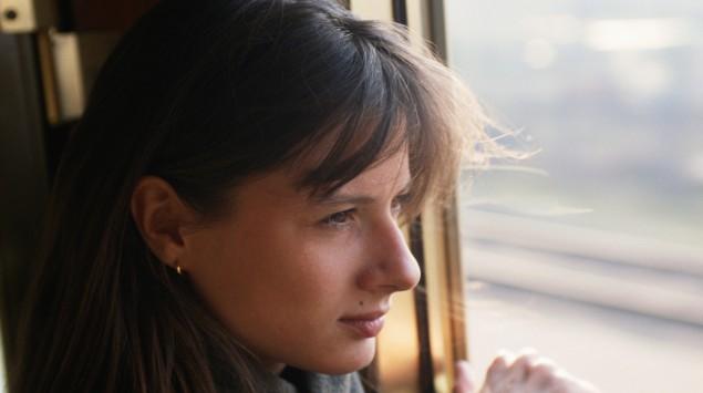 Das Bild zeigt eine Frau, die aus dem Zugfenster guckt.