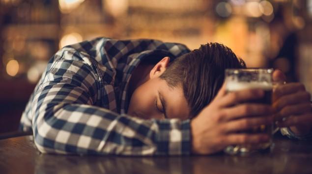 Ein Jugendlicher schläft mit einem Bier in der Hand an der Theke.