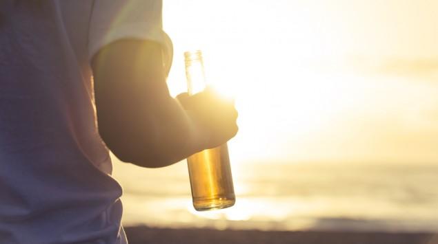 Eine Person hält eine Bierflasche in der rechten Hand, die im Abendlicht schimmert.