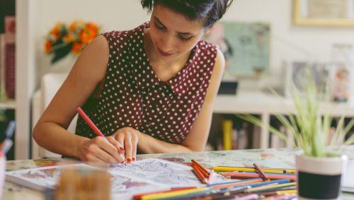 Eine Frau malt Bilder aus.