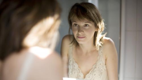 Junge Frau schaut sich im Spiegel an